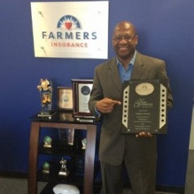 Fabian proudly displays a performance award from Farmers Insurance